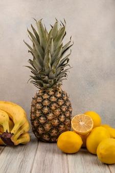 Widok z boku na smaczne owoce, takie jak banany, ananasy i cytryny odizolowane na szarej powierzchni