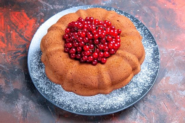 Widok z boku na smaczny talerz ciasta i czerwonych porzeczek na stole
