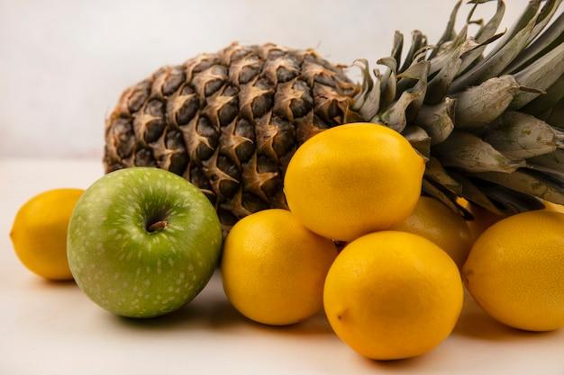 Widok z boku na soczyste owoce, takie jak zielone jabłko ananasa i cytryny na białym tle na białej ścianie