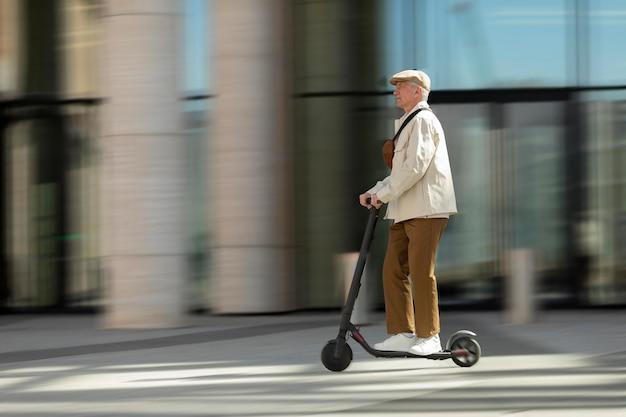Widok z boku na starszego mężczyznę w mieście jadącego na skuterze elektrycznym