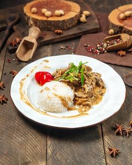 Widok z boku na stroganow wołowy z ryżem na drewnianym stole