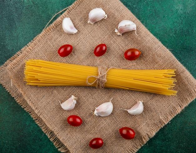 Widok z boku na surowe spaghetti z pomidorkami cherry i czosnkiem na beżowej serwetce