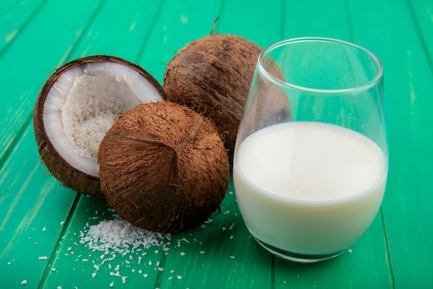 Widok z boku na świeże i brązowe orzechy kokosowe ze szklanką mleka na zielonej powierzchni