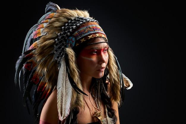 Widok z boku na szamańską kobietę z piórami odwracającymi wzrok odizolowany w studio, kolorowe obrazy na jej twarzy i ciele