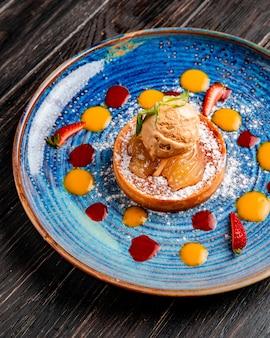Widok z boku na szarlotkę z lodami ozdobioną świeżą truskawką i sosem na talerzu na drewnie