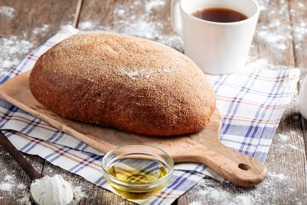 Widok z boku na szary bochenek chleba z oliwą z oliwek