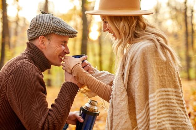 Widok z boku na szczęśliwą parę picia gorącej herbaty w lesie jesienią