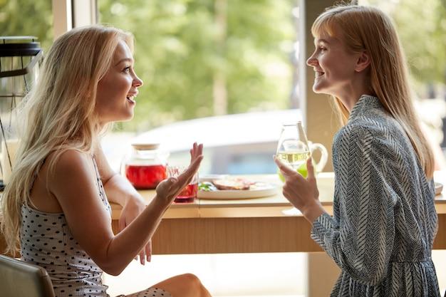 Widok z boku na szczęśliwe blond kobiety rozmawiające i pijące szampana w kawiarni
