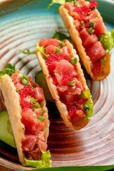 Widok z boku na tacos z łososia z czerwonym kawiorem i zieloną cebulą na talerzu