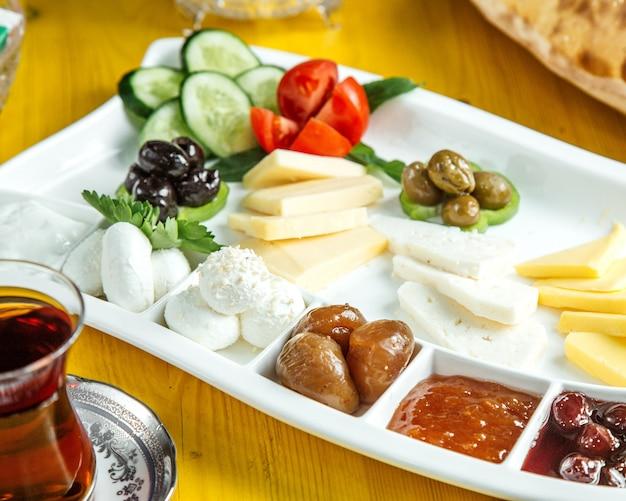 Widok z boku na talerz z jedzeniem śniadaniowym ze świeżymi warzywami, oliwkami, miodem i dżemem, podawane z herbatą