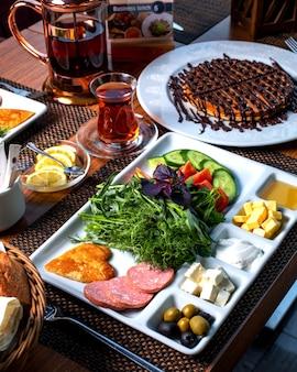 Widok z boku na talerz ze śniadaniowym sałatką ze świeżych warzyw, serowym miodem, smażonymi jajkami i kiełbaskami podawanymi z herbatą i pustynią