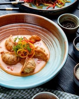 Widok z boku na tradycyjne azjatyckie pierogi z mięsem i warzywami podawane z sosem na talerzu rustykalnym