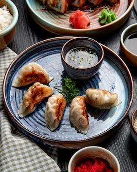 Widok z boku na tradycyjne azjatyckie pierogi z mięsem i warzywami podawane z sosem sojowym na talerzu w stylu rustykalnym
