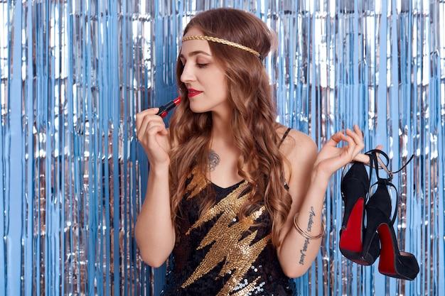 Widok z boku na uroczą dziewczynę z pięknym lokiem, nakłada szminkę i trzymając w rękach buty na wysokich obcasach