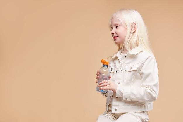 Widok z boku na urocze dziecko albinosa kaukaskiego trzymającego butelkę wody