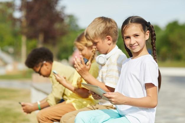 Widok z boku na wieloetniczną grupę dzieci korzystających z tabletów i smartfonów, siedząc w rzędzie na zewnątrz w słońcu, skup się na uśmiechniętej dziewczynie na pierwszym planie, skopiuj przestrzeń