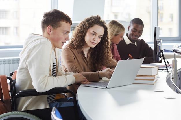 Widok z boku na wieloetniczną grupę studentów korzystających z laptopa podczas nauki w college'u, z chłopcem na wózku inwalidzkim