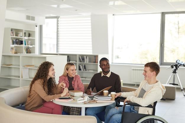 Widok z boku na wieloetniczną grupę studentów studiujących w bibliotece uczelni, na pierwszym planie młody mężczyzna na wózku inwalidzkim,