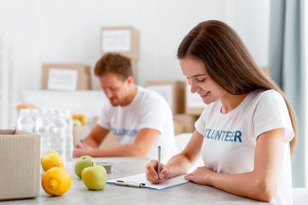 Widok z boku na wolontariuszy pracujących nad darowiznami żywności