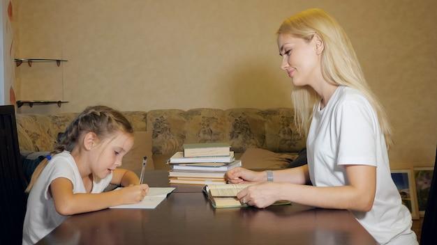 Widok z boku na zadowoloną kobietę i małą dziewczynkę odrabiających razem pracę domową przy stole w salonie
