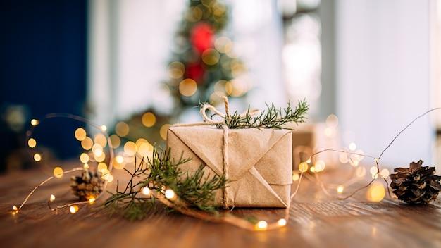 Widok z boku na zawinięte pudełko na prezent na drewnianym stole z girlandami i gałęziami jodły
