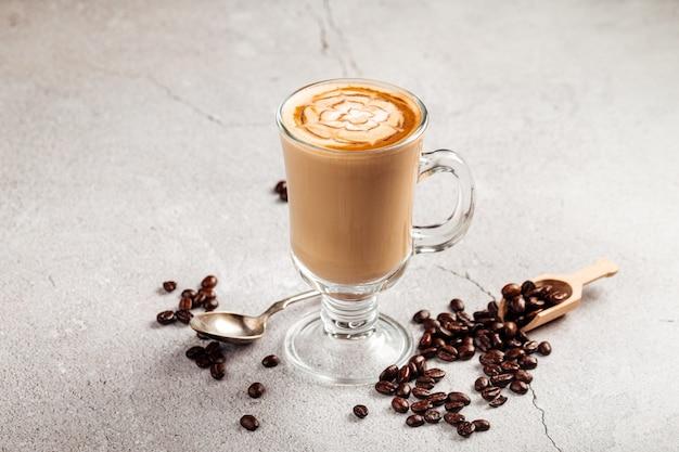 Widok z boku na zdobioną kawę latte w szklanym kubku na betonowym tle