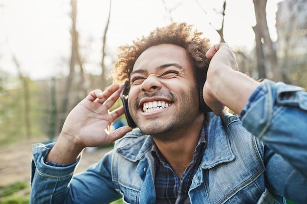 Widok z boku na zewnątrz portret podekscytowanego szczęśliwego afrykańskiego mężczyzny z fryzurą afro, trzymającego słuchawki, słuchając muzyki i uśmiechając się szeroko, zdumiony tym, co słyszy.
