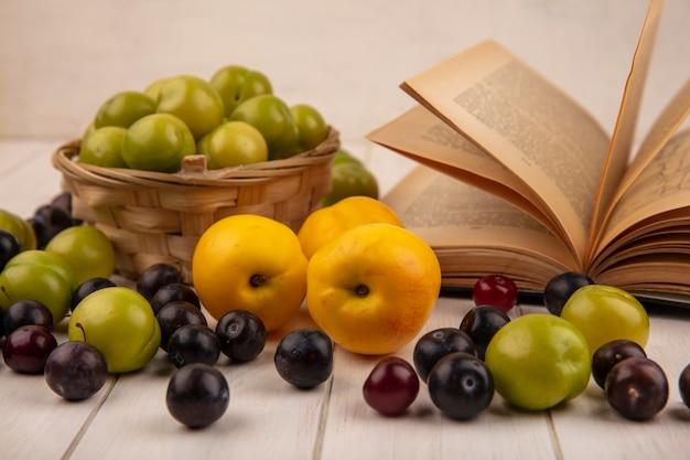 Widok z boku na zielone śliwki wiśniowe w wiadrze z żółtymi słodkimi brzoskwiniami z czerwonymi wiśniami na białym tle na białym tle