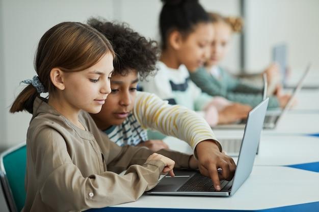 Widok z boku na zróżnicowaną grupę dzieci siedzących w rzędzie w klasie szkolnej i korzystających z laptopów