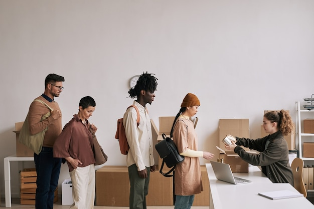 Widok z boku na zróżnicowaną grupę osób stojących w kolejce podczas akcji pomocy i darowizn, miejsce kopiowania