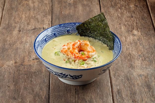 Widok z boku na zupę matcha ramen z langustynkami