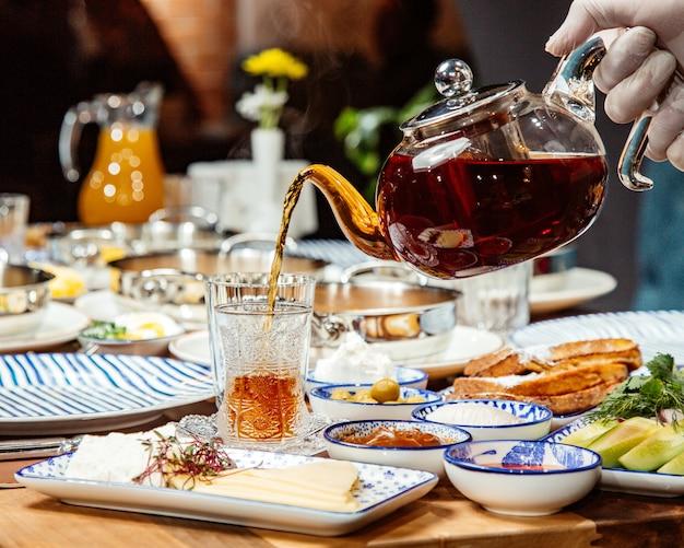 Widok z boku nalewania czarnej herbaty do szklanki