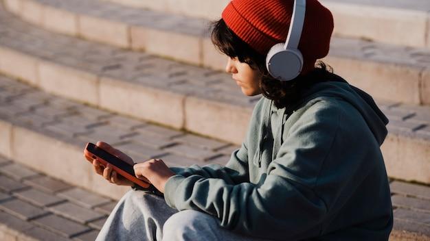 Widok z boku nastolatka na zewnątrz przy użyciu smartfona i słuchania muzyki na słuchawkach