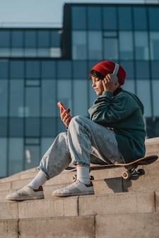 Widok z boku nastolatka na zewnątrz, słuchanie muzyki na słuchawkach podczas korzystania ze smartfona