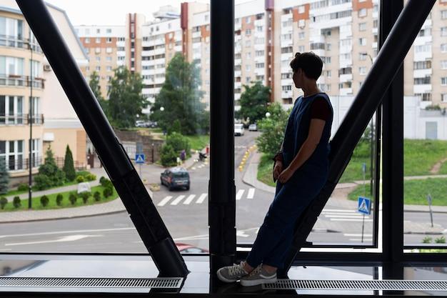 Widok z boku nastolatka patrząc przez okno