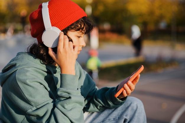 Widok z boku nastolatka, słuchanie muzyki na słuchawkach podczas korzystania ze smartfona