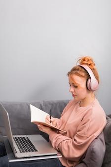 Widok z boku nauczycielki z programem i laptopem podczas zajęć online