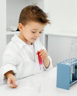 Widok z boku naukowca-chłopca w laboratorium z probówek eksperymentujących
