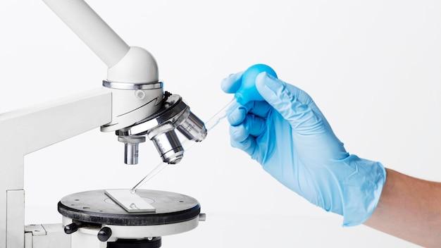 Widok z boku naukowca umieszczającego substancję pod mikroskopem
