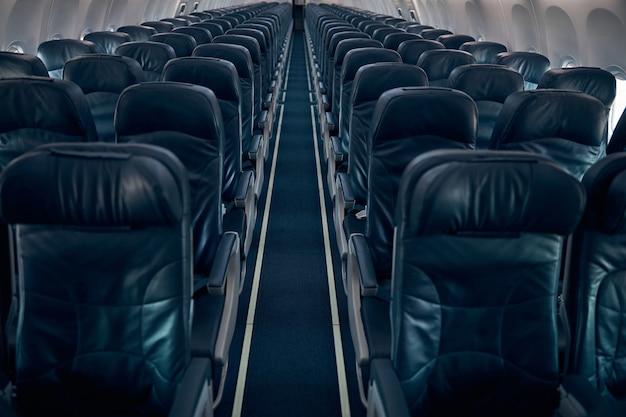 Widok z boku niebieskich siedzeń w kabinie samolotu pasażerskiego