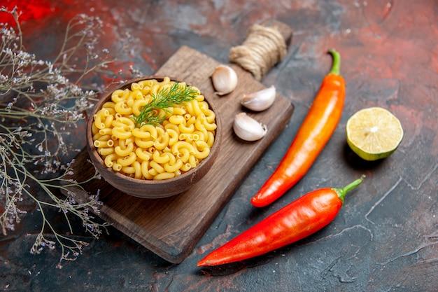 Widok z boku niegotowanych makaronów w brązowej misce i czosnku na drewnianej desce do krojenia papryka cytryna na stole mieszanym kolorów