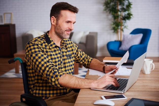 Widok Z Boku Niepełnosprawnego Biznesmena Korzystającego Z Laptopa W Domowym Biurze Premium Zdjęcia