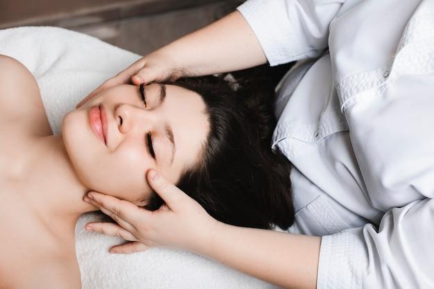 Widok z boku niesamowitej kobiety opierającej się na łóżku spa z zamkniętymi oczami, poddawanej terapii pielęgnacji skóry twarzy przez kosmetologa w centrum odnowy biologicznej