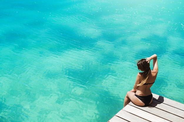 Widok z boku niesamowitej wysportowanej kobiety siedzącej na molo z włosami