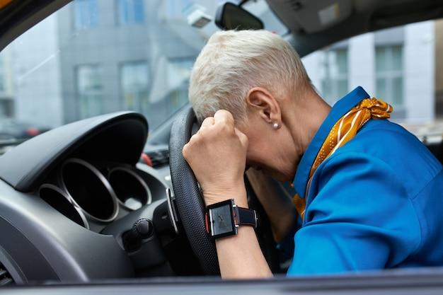 Widok z boku nieszczęśliwej, zestresowanej kobiety w średnim wieku ściskającej pięści i opierającej głowę na kierownicy, utkniętej w korku, spóźniającej się do pracy lub wypadku samochodowego, siedzącej na siedzeniu kierowcy