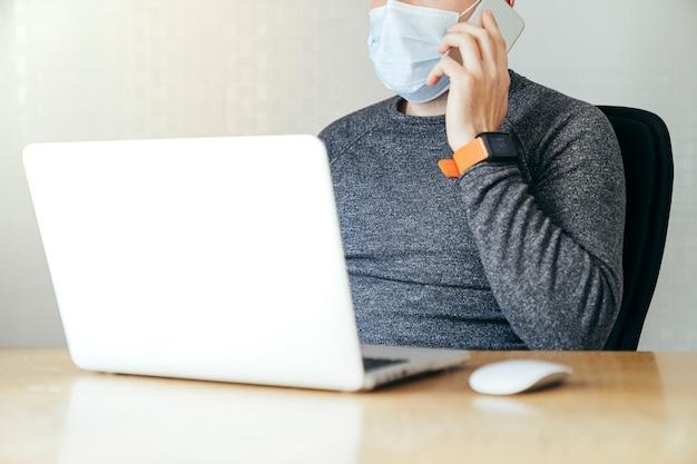 Widok z boku nieznanego młodego człowieka noszącego maskę i szary jersey. on jest przed laptopem. on dzwoni. on pracuje nad drewnianym stołem.