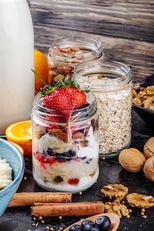 Widok z boku nocnych owsów ze świeżymi jagodami, truskawkami i jogurtem w szklanym słoju na stole