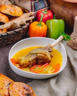 Widok z boku nogi kaczki w bulionie z warzywami w białym misce