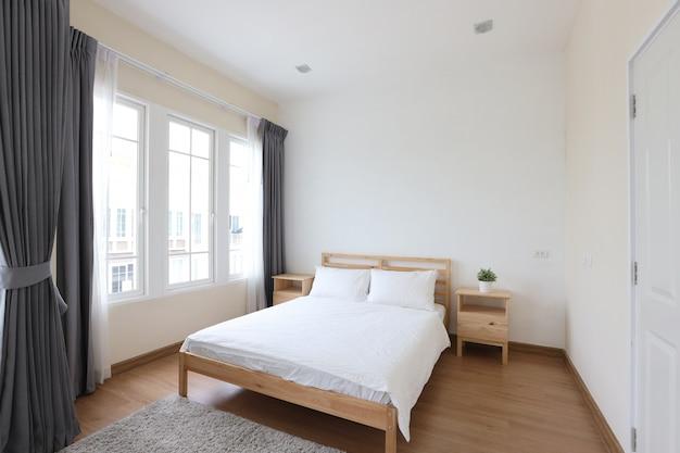 Widok z boku nowego nowoczesnego białego drewnianego łóżka w białej sypialni z miękkim i jasnym światłem