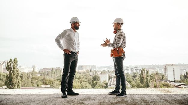 Widok z boku o niskim kącie profesjonalnego brygadzisty omawiającego plany pracy z inżynierem podczas spotkania na placu budowy